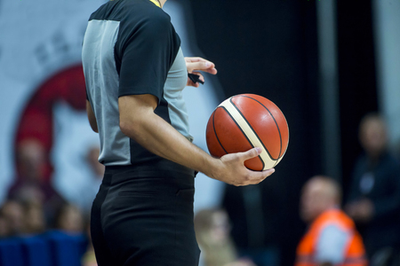 Basketball referee holding a basketball at a game in a crowded sports arena Archivio Fotografico