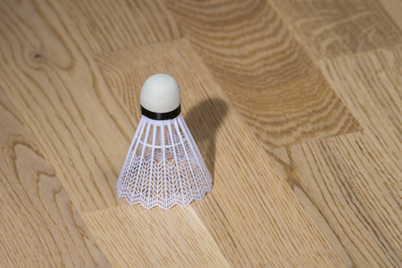 Badminton shuttlecock isolated on sports hall parquet background