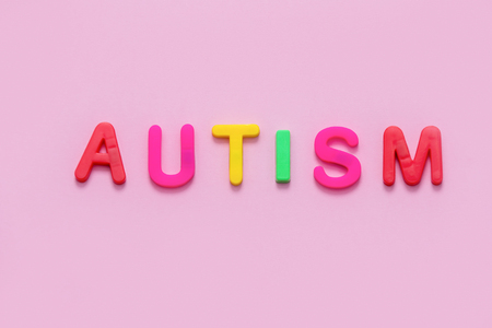 Word AUTISM on pink background, top view Stock Photo