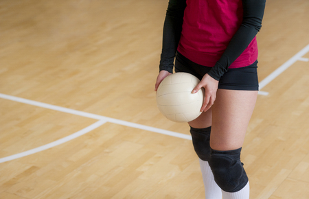 Volleyball player is a female athlete getting ready to serve the ball