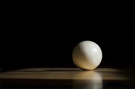Pavimento in legno del campo da pallavolo con palla isolata sul nero con copia-spazio