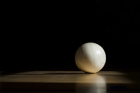 Volleyball court wooden floor with ball isolated on black with copy-space