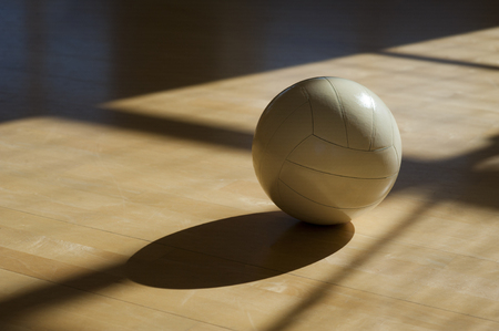 Volleyball on the parquet with black background