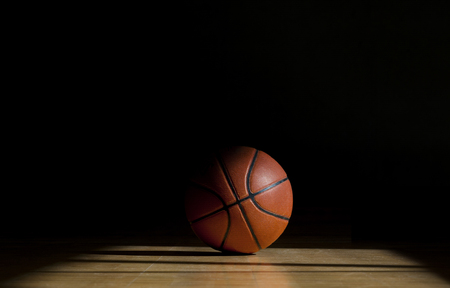 Pallone da basket sul parquet con sfondo nero Archivio Fotografico