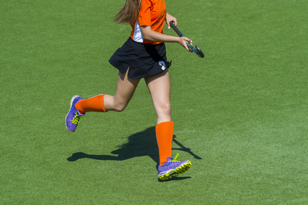 Field hockey player, in possesion of the ball, running over an astroturf pitch, looking for a team mate to pass to 스톡 콘텐츠