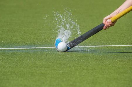 hockey player with ball in attack playing field hockey game