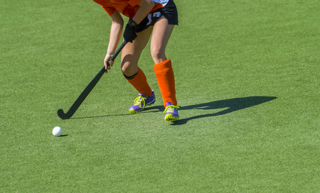 Young hockey player woman with ball in attack playing field hockey game Imagens
