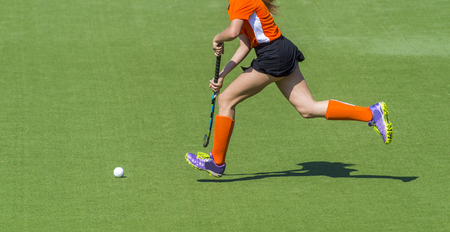 Young hockey player woman with ball in attack playing field hockey game 写真素材