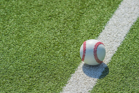 White ball for playing baseball on the grass background