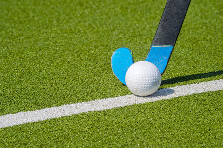 Field hockey stick and ball on green grass Foto de archivo