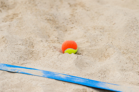 tennis ball on the sand at the beach close up