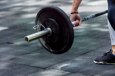 crossfit woman preparing for her weightlifting workout with a heavy dumbbell