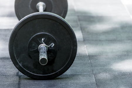 Heavy barbell on the floor of a gym studio copyspace