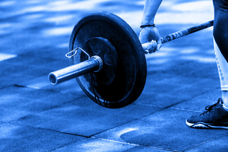 crossfit woman preparing for her weightlifting workout with a heavy dumbbell. Blue color