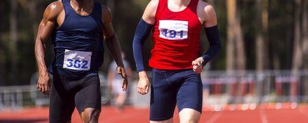 Athlètes masculins sprintant. Deux hommes en vêtements de sport courent sur la piste de course dans un stade professionnel
