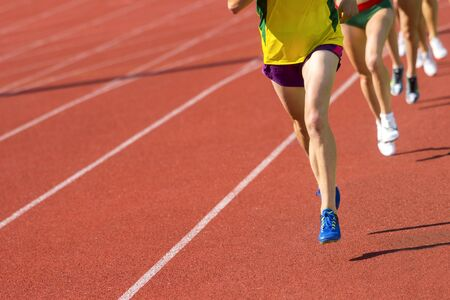 Athletics people running on the track field. Sunny day
