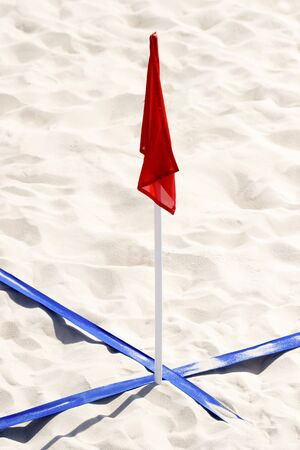 beach soccer court up close and in detail with blue plastic line marker and red flag