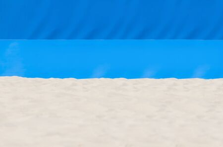 Football, volleyball, handball summer sport. Sandy beach on blue background with copy space for text