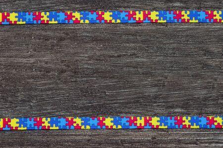 Welt-Autismus-Bewusstseinstag mit Puzzleband auf Holzuntergrund