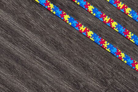 World Autism awareness day with Puzzle ribbon on wooden background