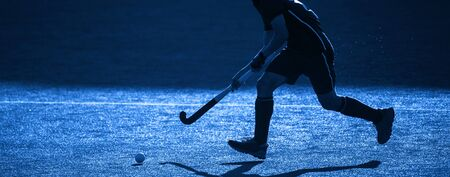 A Field Hockey Player About To Pass The Ball. Blue filter. Imagens