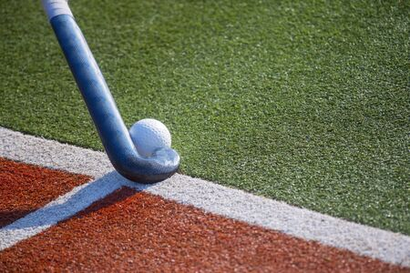 Field Hockey Stick and Ball on fake Grass With Copy Space. Stock Photo