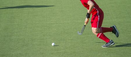 Hockey player with ball in attack playing field hockey game Stock Photo