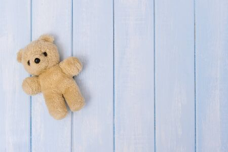 Small teddy bear on blue pastel wooden background, top view