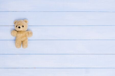 Small teddy bear on blue wooden background, top view Stock Photo