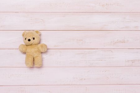 Small teddy bear on pink wooden background, top view