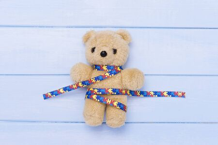 World Autism Awareness day, mental health care concept with teddy bear and ribbon puzzle pattern. On blue background
