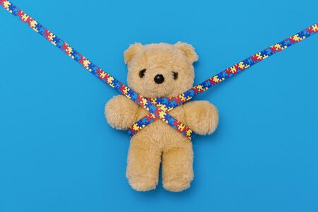 World Autism Awareness day, mental health care concept with teddy bear and ribbon puzzle pattern. On blue background Stock Photo
