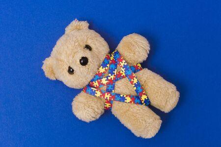 Día mundial de la conciencia del autismo, concepto de atención de la salud mental con oso de peluche y patrón de rompecabezas de cinta Sobre fondo azul