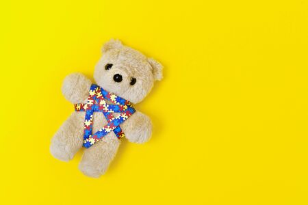 World Autism Awareness day, mental health care concept with teddy bear and ribbon puzzle pattern. On yellow background