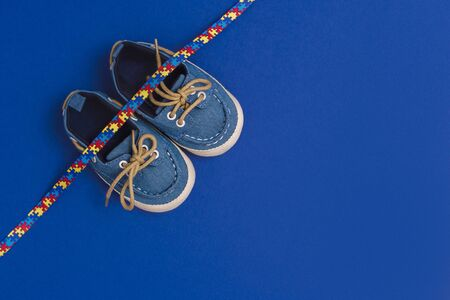 World Autism Awareness day, mental health care concept with blue baby shoes and ribbon puzzle pattern. On blue background