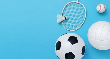 Assorted sports equipment including a basketball, soccer ball, volleyball, baseball, badminton racket on a light blue background Stock Photo