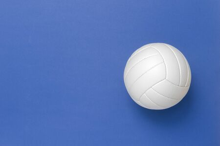 White volleyball leather ball on blue background. Top view.
