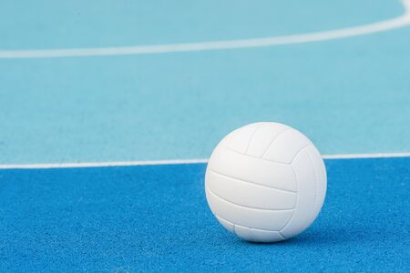 Volleyball ball on blue playground with white line