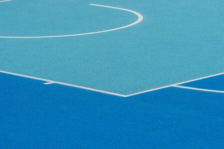 Abstract, blue background of newly made outdoor basketball court. Visible asphalt texture, freshly painted lines