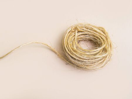 Skein of jute twine isolated on light beige natural background