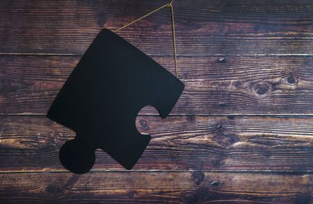 Puzzle piece on wooden background. Autism Spectrum Disorder (ASD). Autism awareness. Concept of autism word.