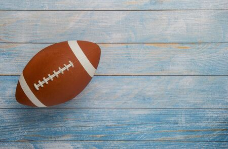 American football ball on wooden background