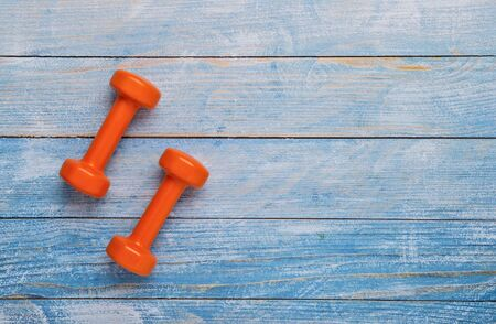 Orange dumbbell on wooden table. Fitness healthy and sport concept