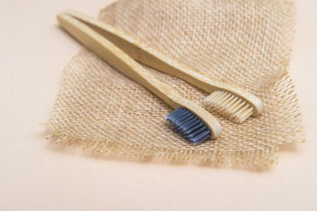 Bamboo tooth brush on light beige natural background Banco de Imagens