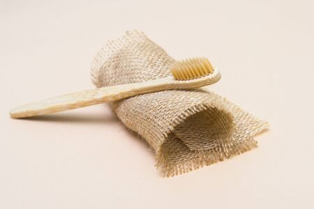 Bamboo tooth brush on light beige natural background 写真素材