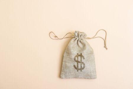 Money bag on light beige natural background