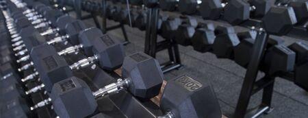 Close up many metal dumbbells on rack in sport fitness center Banco de Imagens