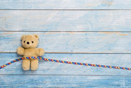 World Autism Awareness day, mental health care concept with teddy bear and ribbon puzzle pattern. On blue background Banco de Imagens