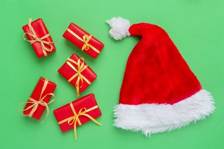 Gift boxes with santa hat on green background