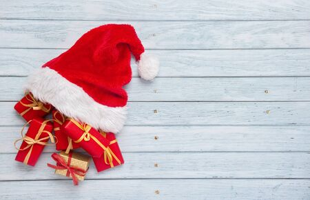 Gift boxes with santa hat on wooden background Stockfoto